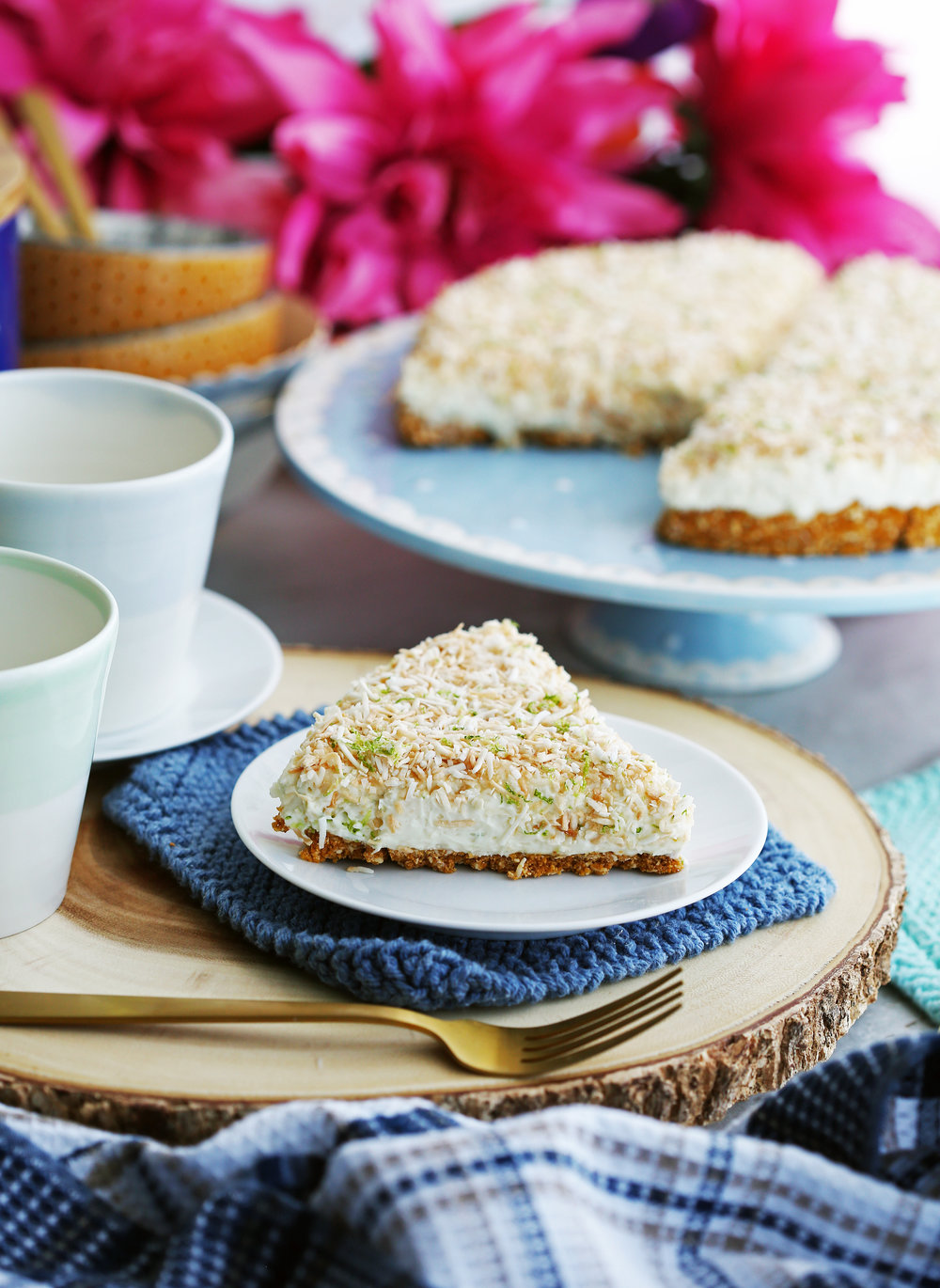 A slice of no-bake coconut lime mascarpone cheesecake on a white plate with more cheesecake on a cake platter behind it.