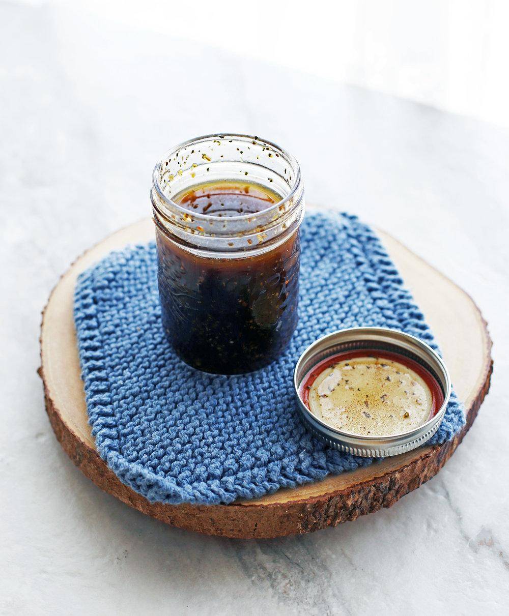 A mason jar containing homemade Dijon-balsamic vinaigrette.