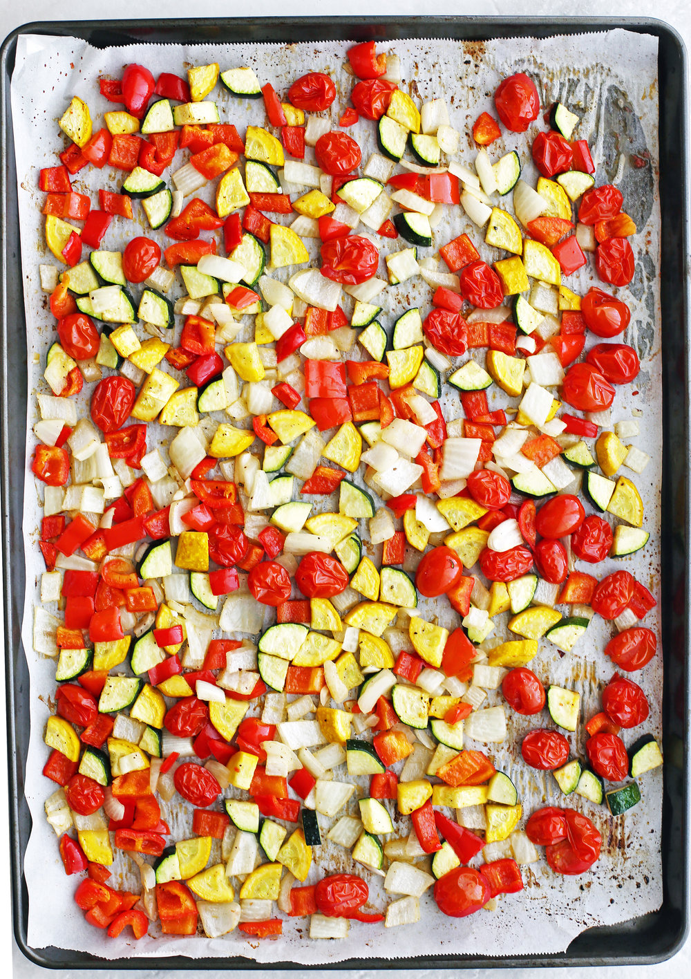 Roasted tomatoes, chopped zucchini, yellow squash, bell peppers, and onions on a baking sheet.