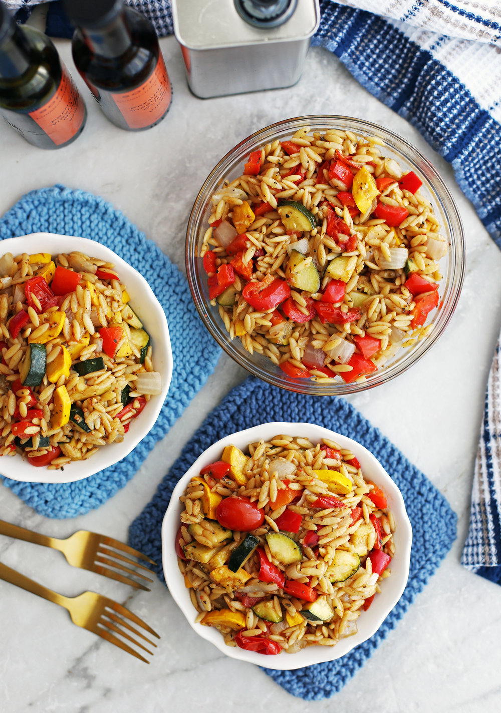 Three bowls containing colourful roasted summer vegetable and orzo pasta salad with Dijon-balsamic vinaigrette.