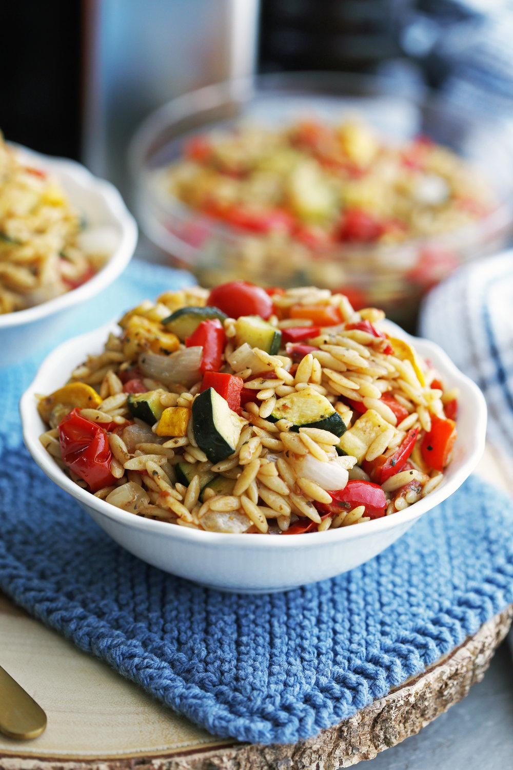 A small white bowl containing Roasted summer vegetable and orzo pasta salad with Dijon-balsamic vinaigrette