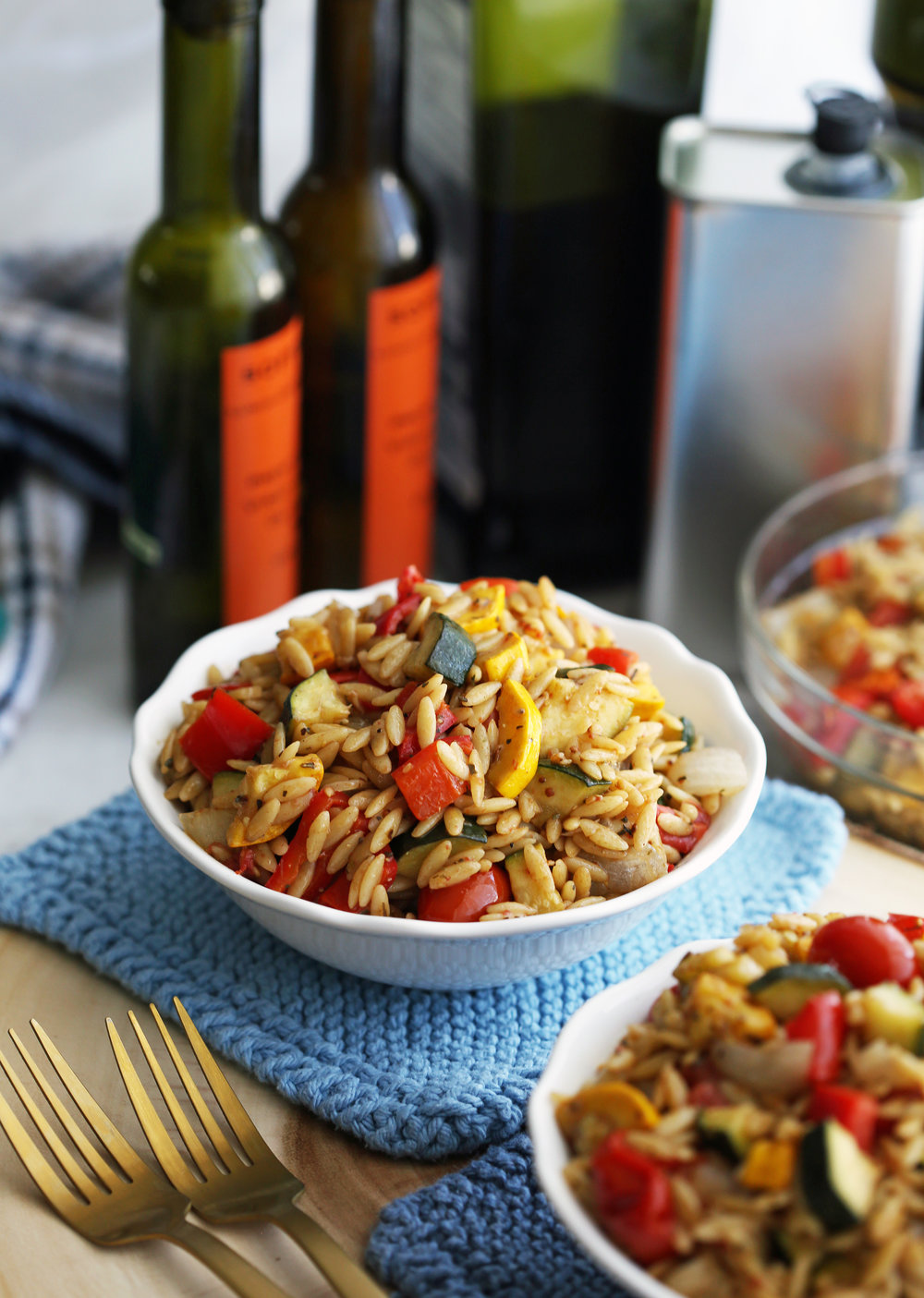 Roasted summer vegetable and orzo pasta salad with Dijon-balsamic vinaigrette in a small white bowl.
