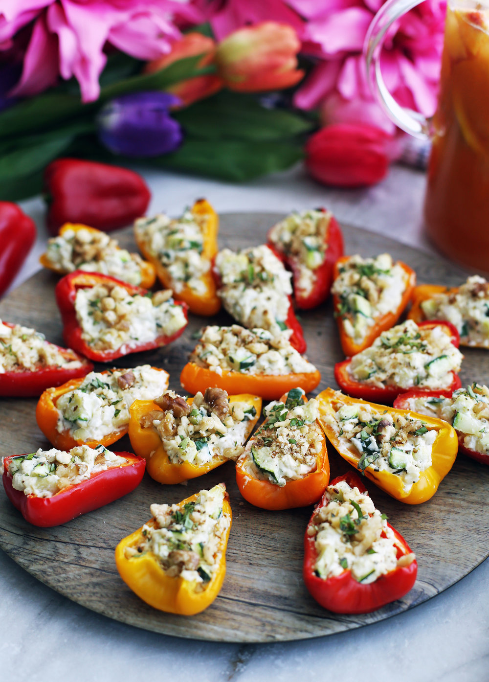 Baked mini bell peppers halves filled with a zucchini, onion, and cream cheese filling on a round wooden platter.