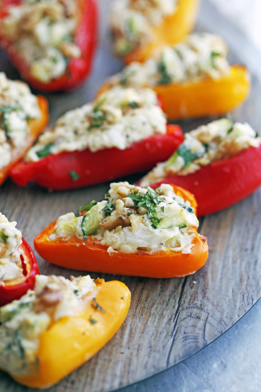 A closeup of a zucchini cream cheese mini bell pepper topped with chopped walnuts and basil on a wooden platter.