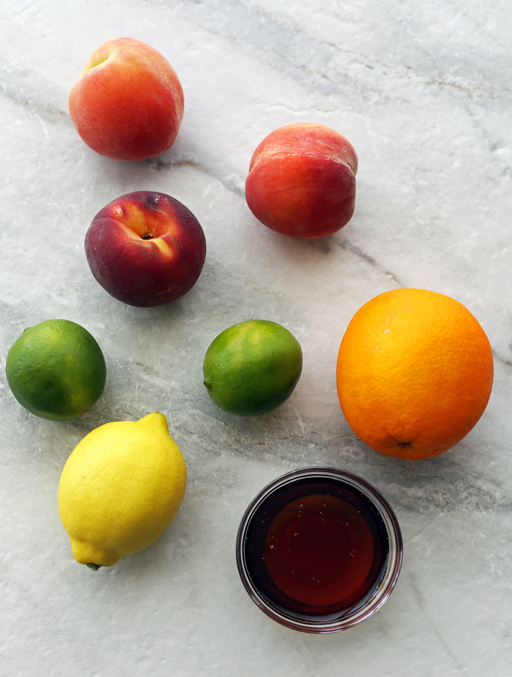 Three peaches, two limes, an orange, a lemon, and a bowl of maple syrup.