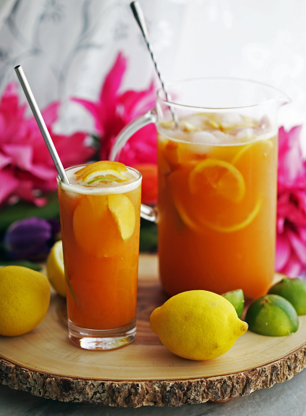 Maple peach citrus juice with fruit slices and ice in a tall drinking glass and glass container.