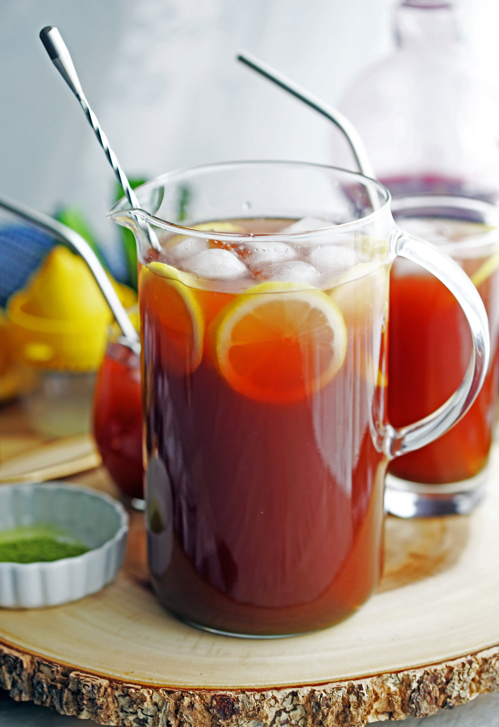 A large glass pitcher full of pomegranate matcha iced tea with lemon slices and ice.