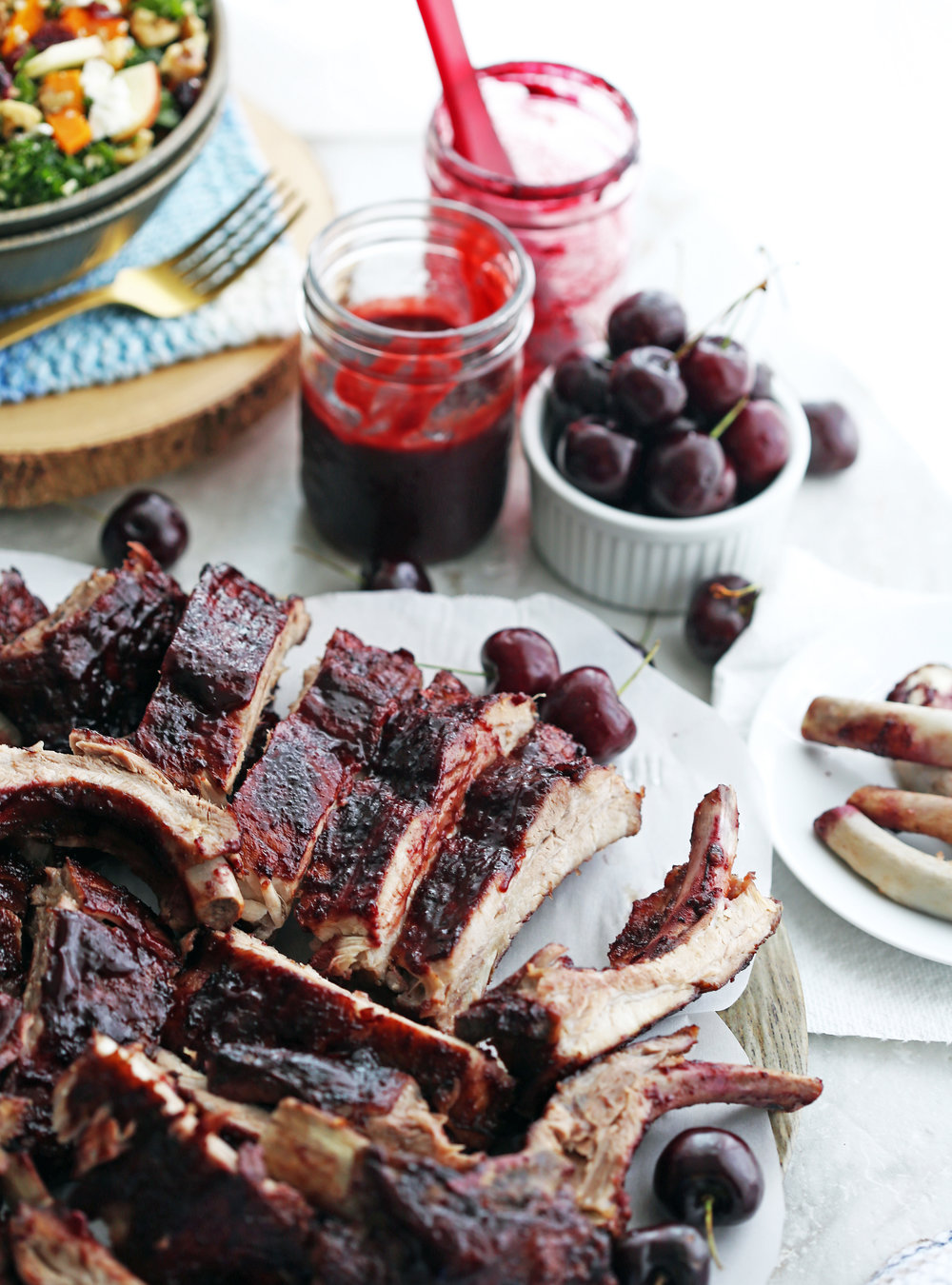A platter of Baby Back Ribs covered with cherry chipotle sauce, a jar of sauce, and a bowl of fresh cherries on the side.