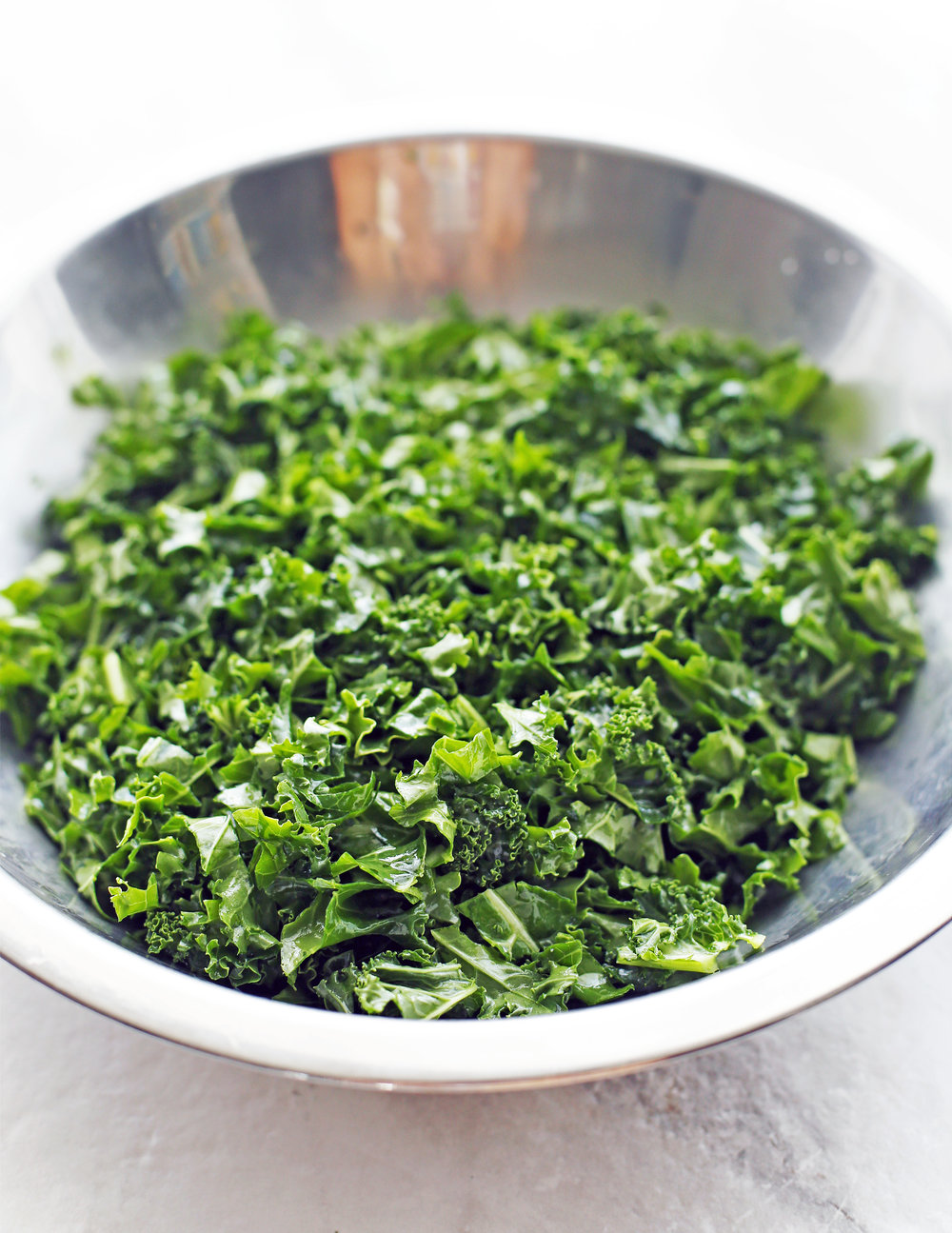 Chopped green curly kale in a metal bowl.