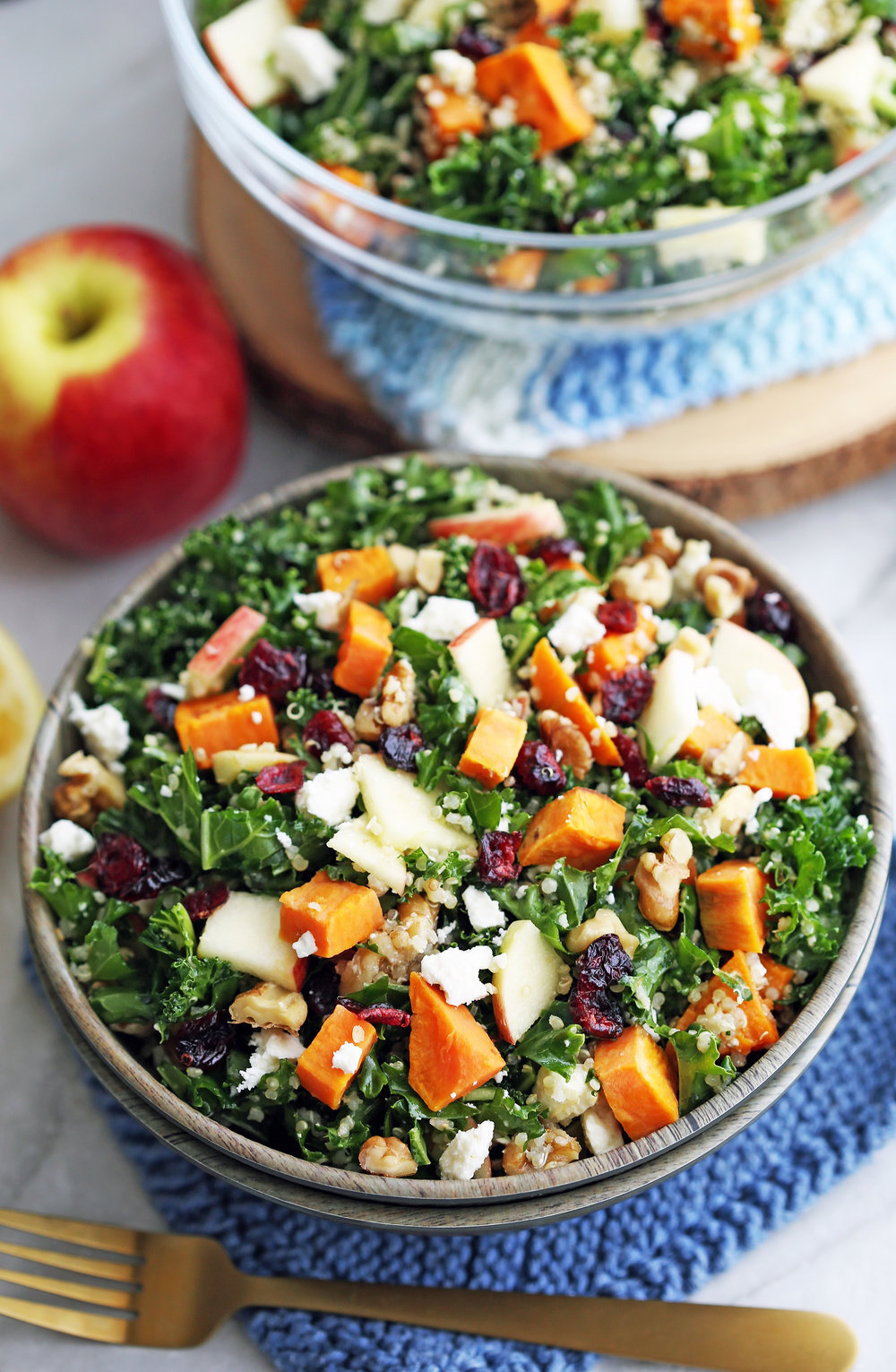 A closeup of a bowl of a kale salad with pieces of sweet potato, quinoa, apples, dried cranberries, feta, and walnuts.