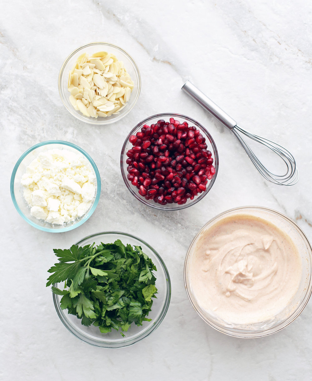 Bowls containing feta cheese, parsley, pomegranate arils, slivered almonds, and paprika yogurt dressing.