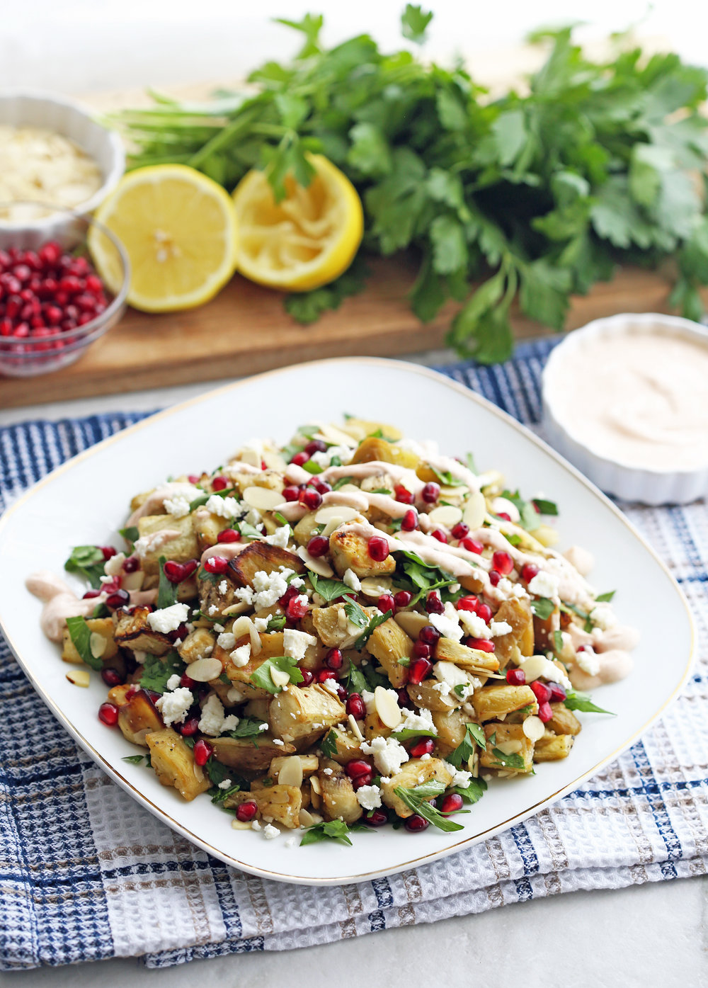 A white plate full of roasted eggplant pomegranate feta salad with smoked paprika yogurt dressing drizzled on top.