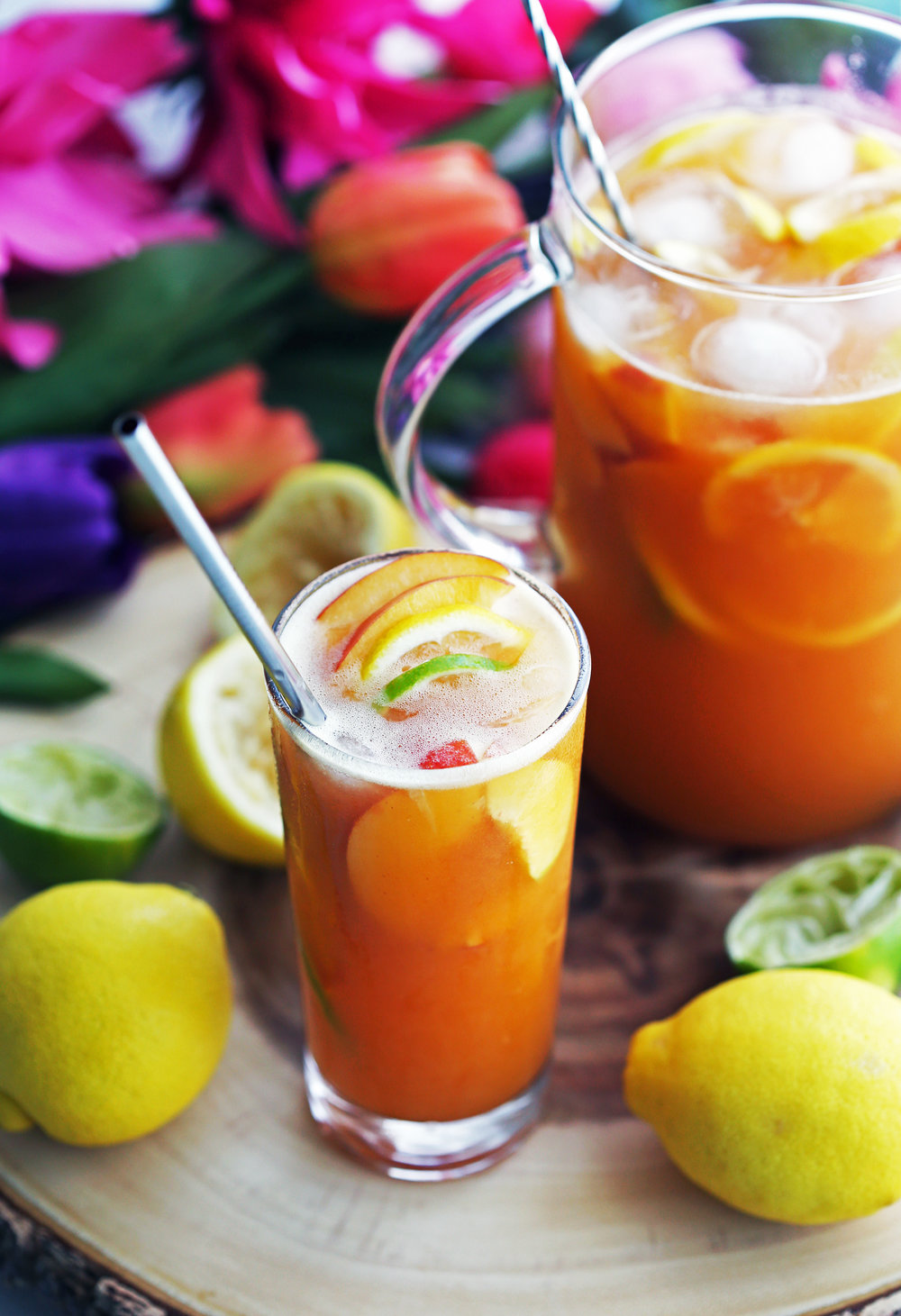 A drinking glass and glass container full of maple peach citrus juice with fruit slices and ice.