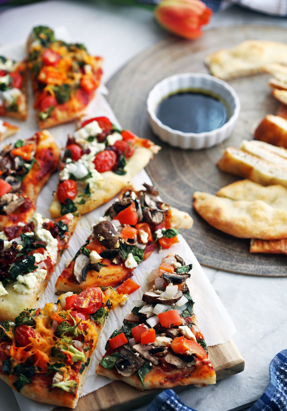 Two platters containing flatbread pizza with various toppings and plain flatbread sliced into pieces.