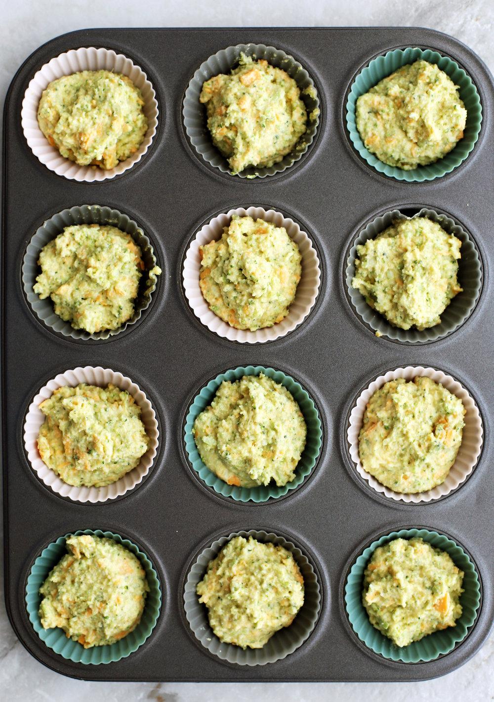 Broccoli Cheddar Cornbread Muffin batter scooped into a muffin pan.