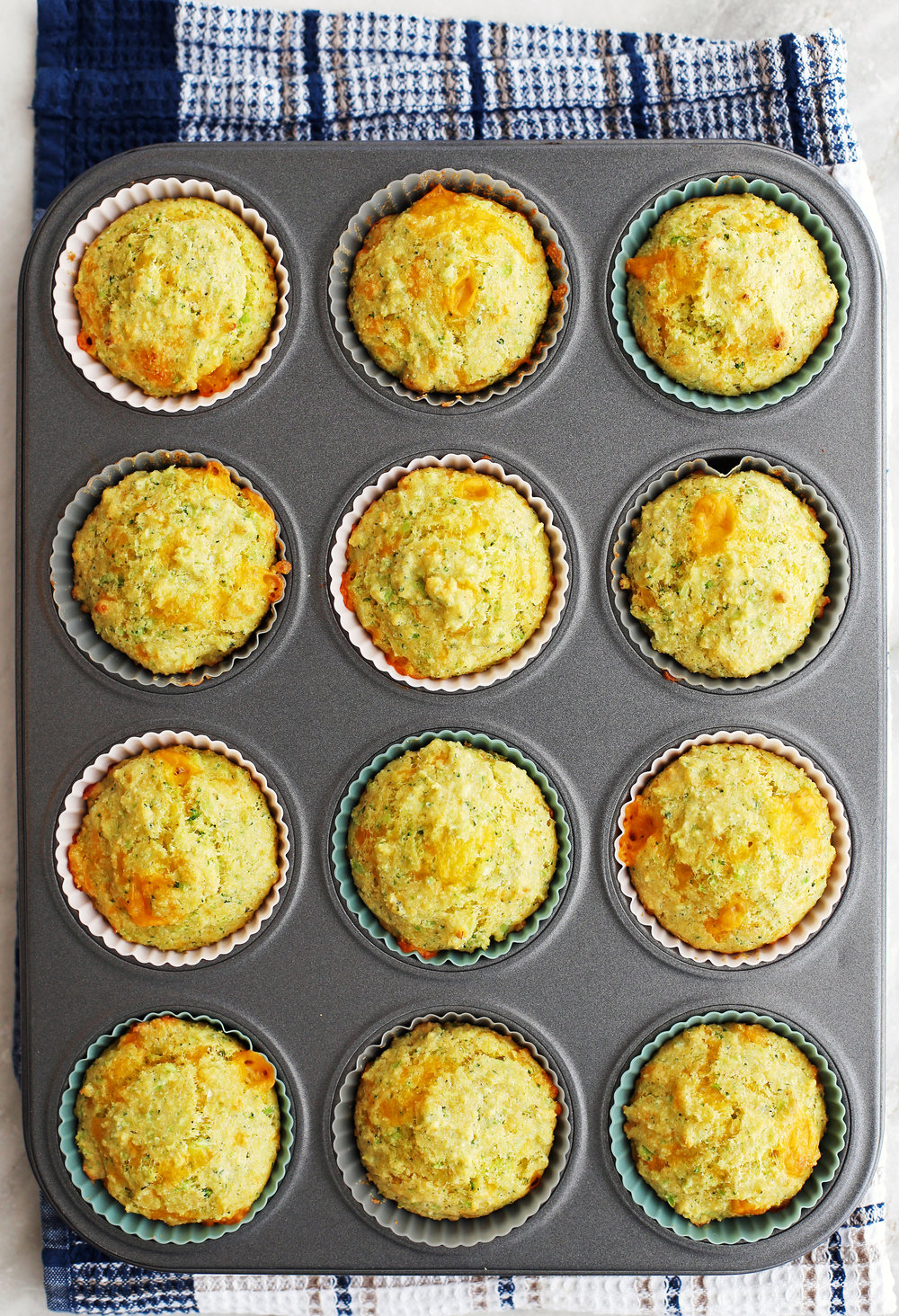 Twelve Broccoli Cheddar Cornbread Muffins in a muffin pan.