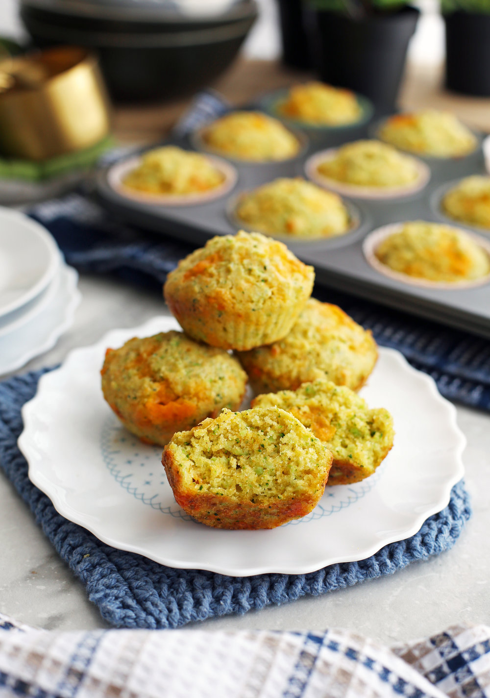Four Broccoli Cheddar Cornbread Muffins with one cut in half on a white plate with more in a muffin pan behind them.