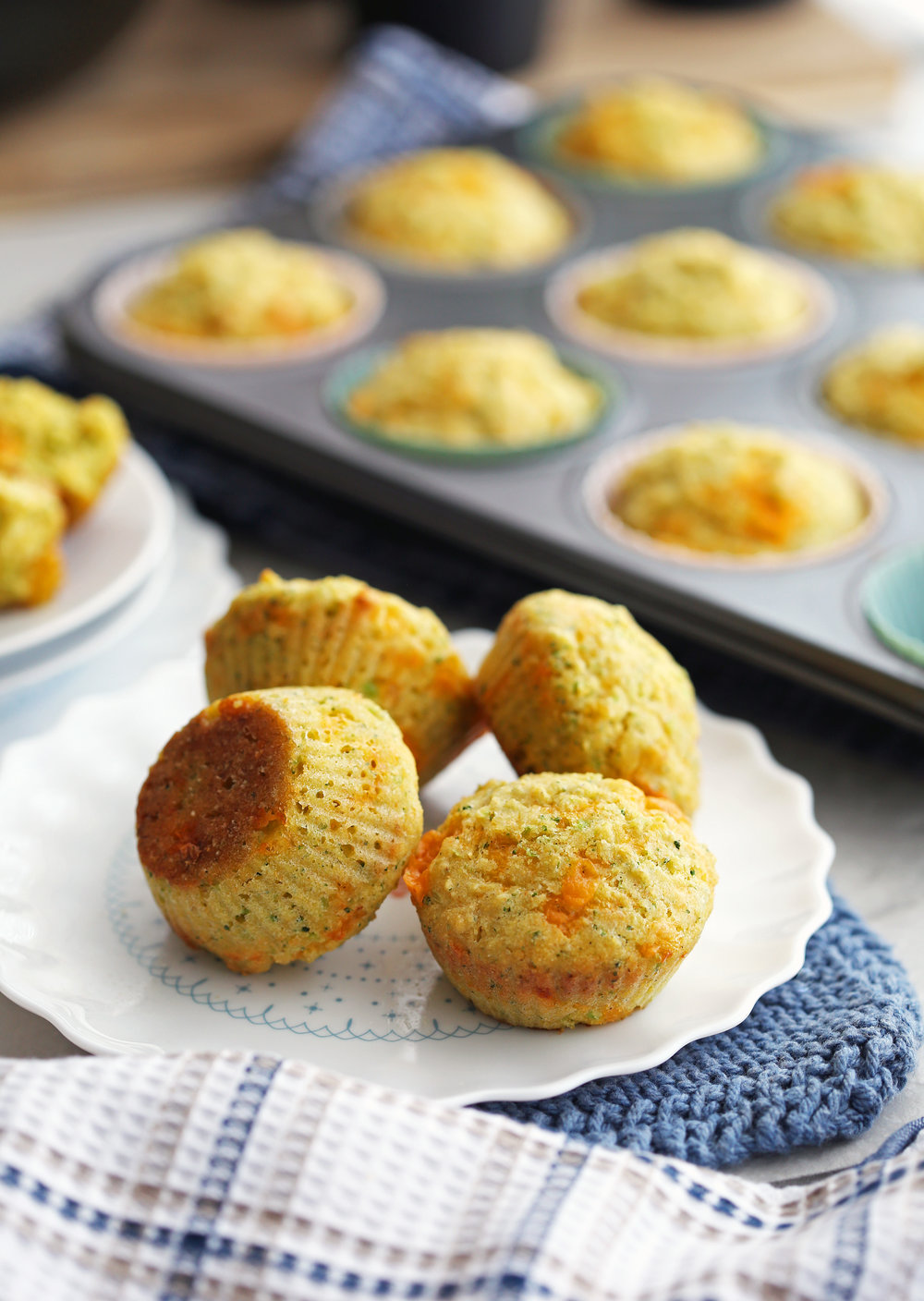 Four Broccoli Cheddar Cornbread Muffins on a white plate with more muffins in a muffin pan behind them.