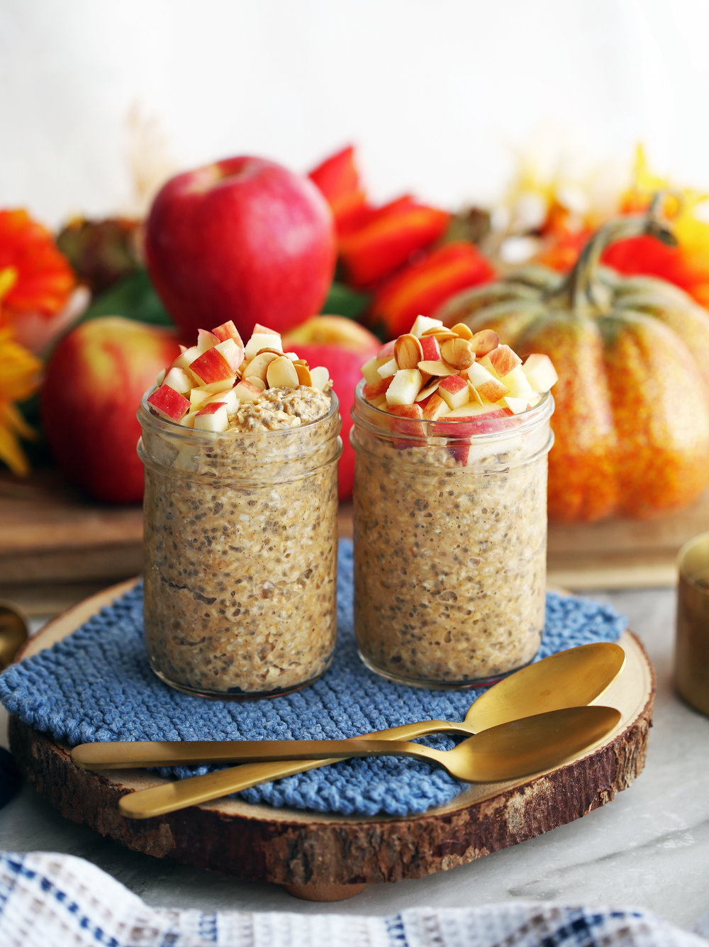 Chai spiced pumpkin overnight oats topped with diced apples in two mason jars on a wooden platter with two spoons.