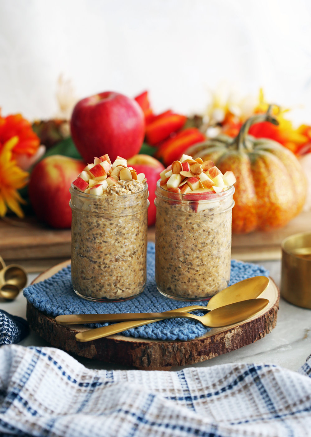 Chai spiced pumpkin overnight oats topped with diced apples and slivered in two mason jars.