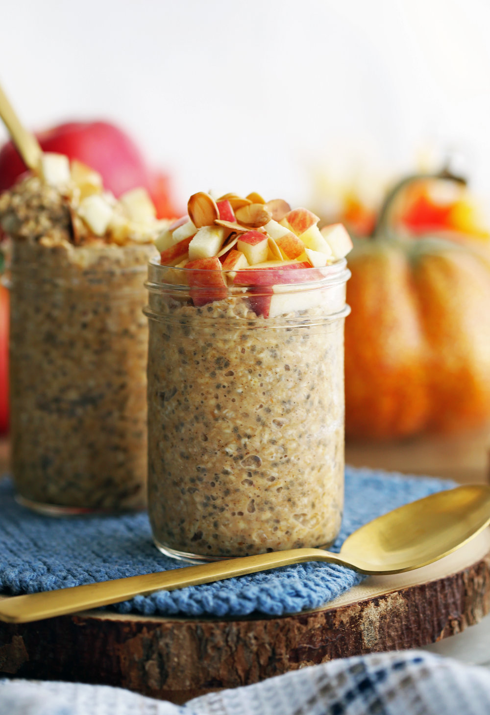 Chai spiced pumpkin overnight oats with apples and slivered almonds in two mason jars with a spoon on the side.