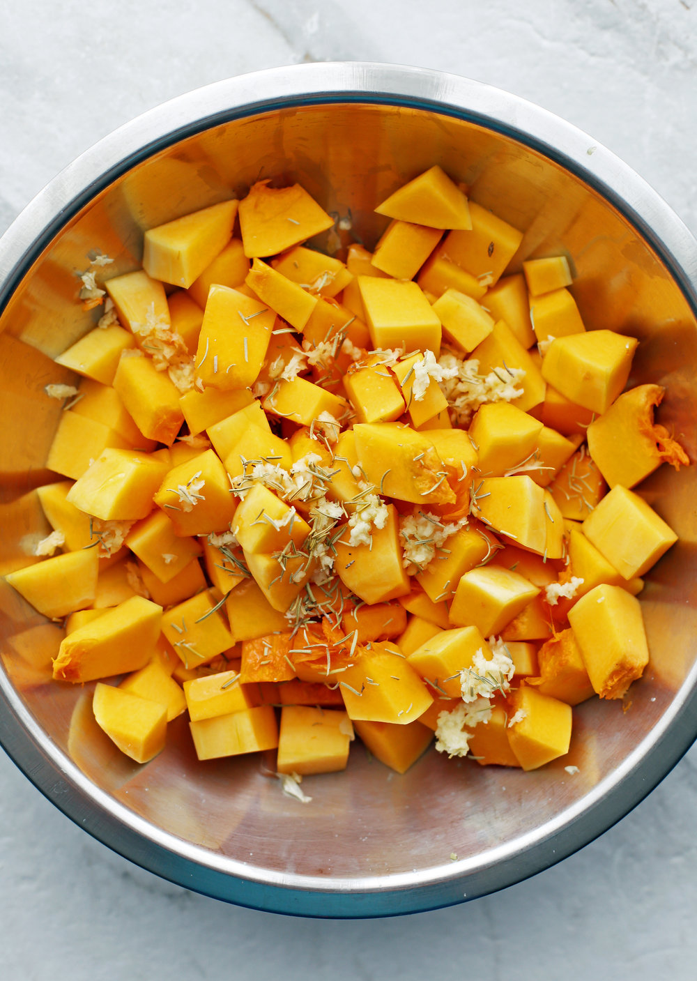 A metal bowl containing chopped butternut squash, garlic, herbs, and olive oil.