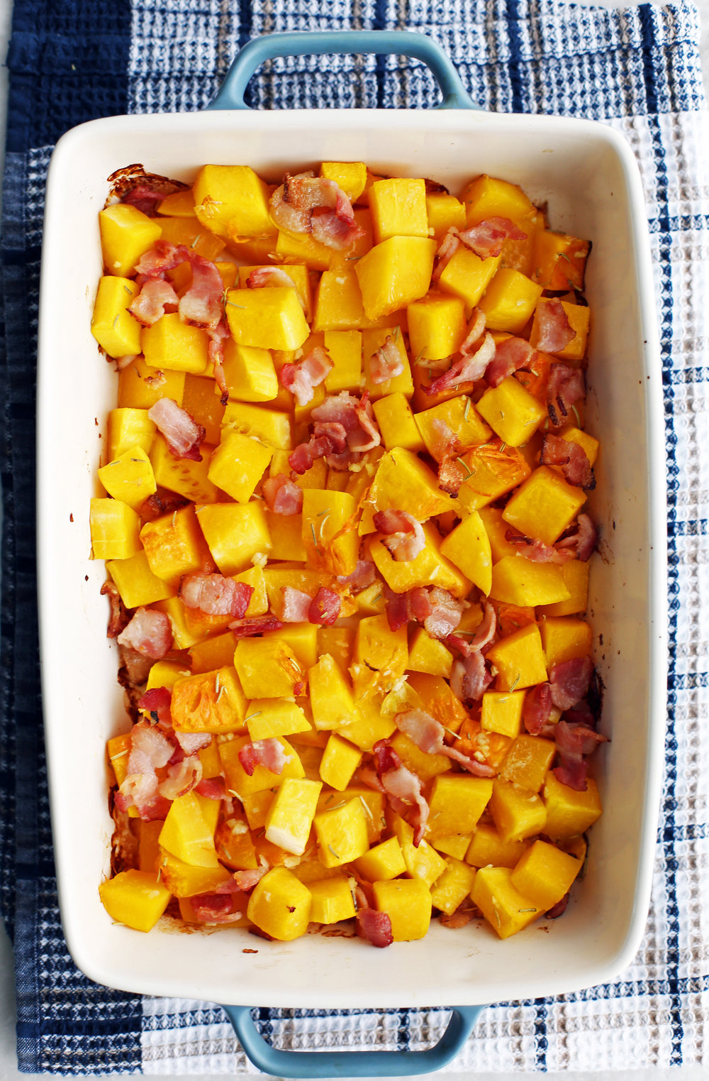 Baked butternut squash and chopped bacon in a large baking dish.