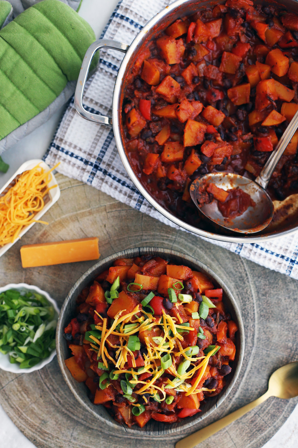 Roasted Butternut Squash and Black Bean Chili in a wooden bowl and in a large metal pot.