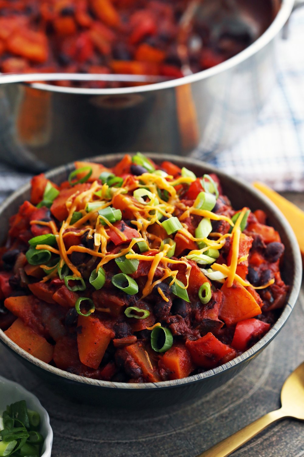 A wooden bowl containing Roasted Butternut Squash and Black Bean Chili with more chili in a large pot behind it.