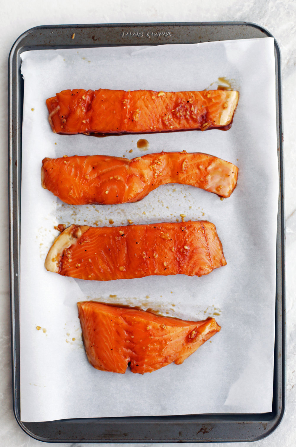 Four maple-soy marinated raw salmon fillets on a baking sheet.