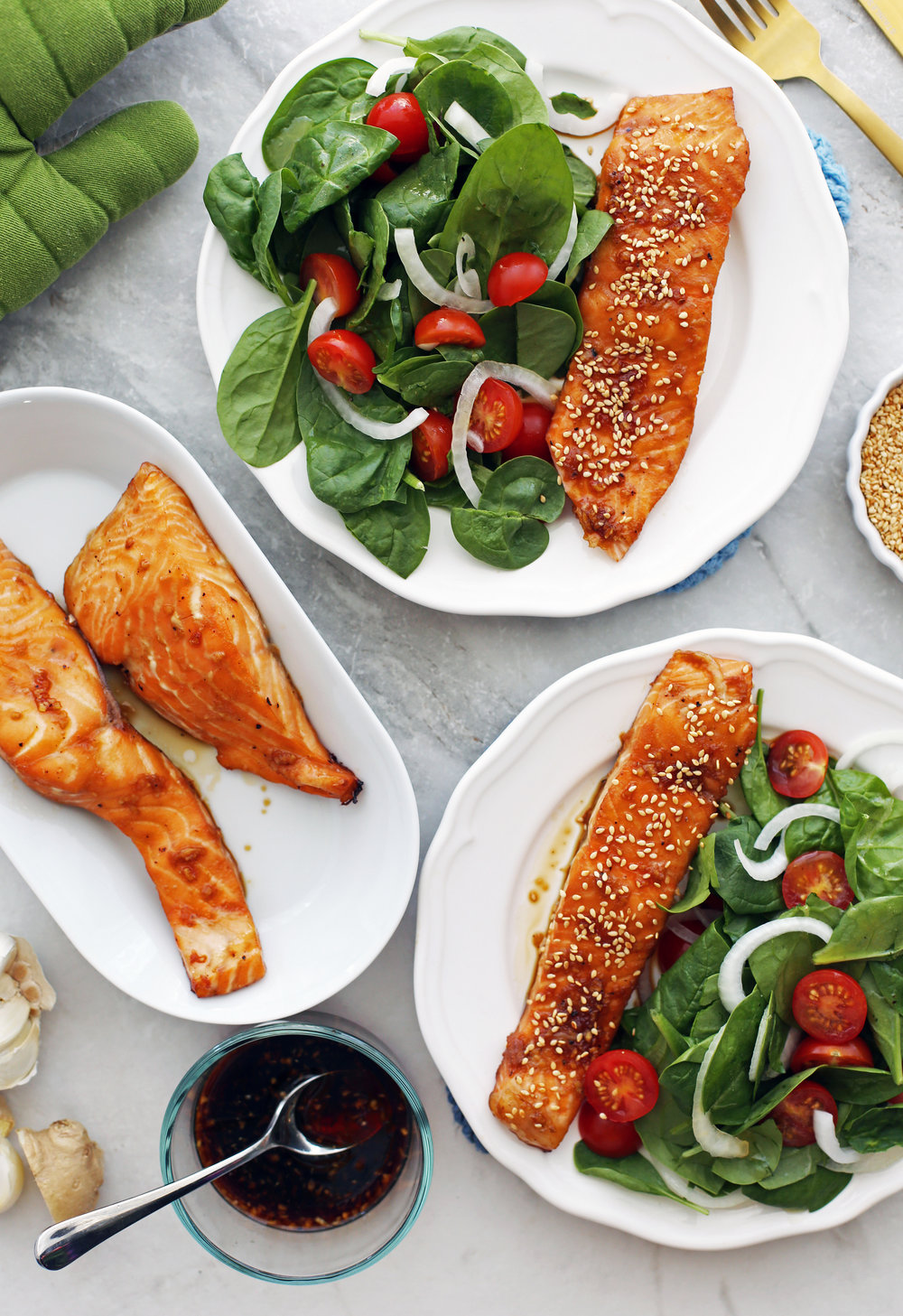 Overhead view of three white plates containing maple-soy baked salmon and spinach salad.