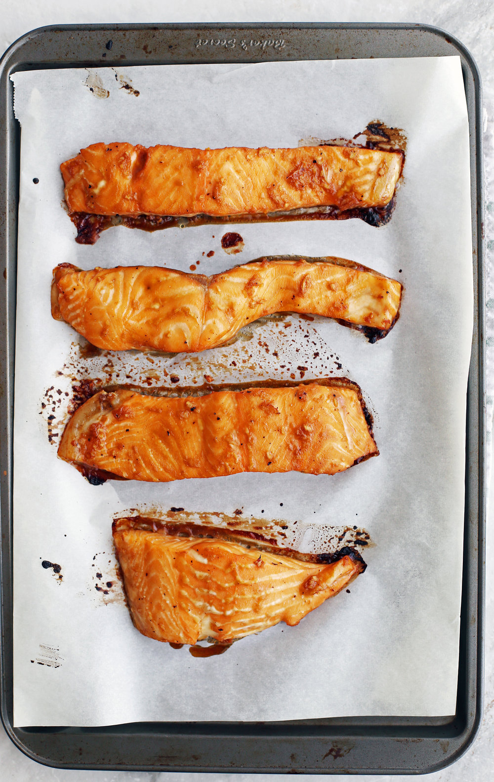 Four maple-soy baked salmon fillets on a baking sheet.
