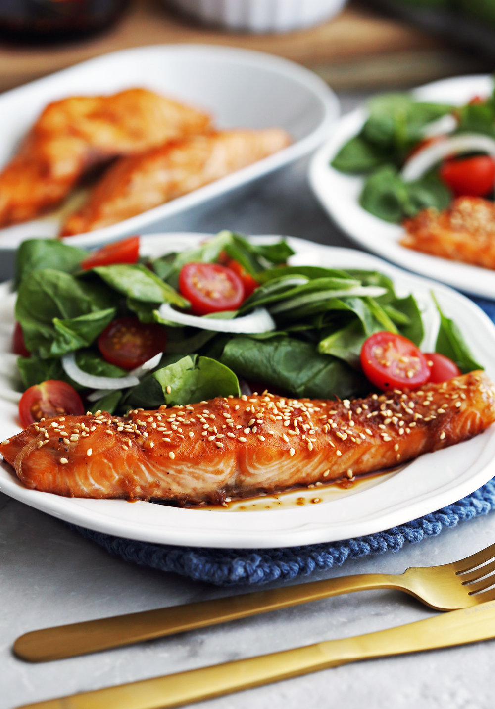 Maple-Soy Baked Salmon topped with sesame seeds with green spinach salad on a white plate.