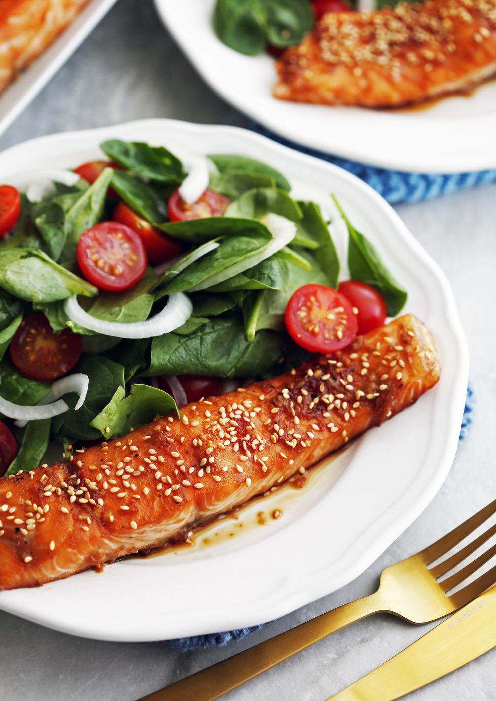 Maple-Soy Baked Salmon with green spinach salad on a white plate with a fork and knife beside it.