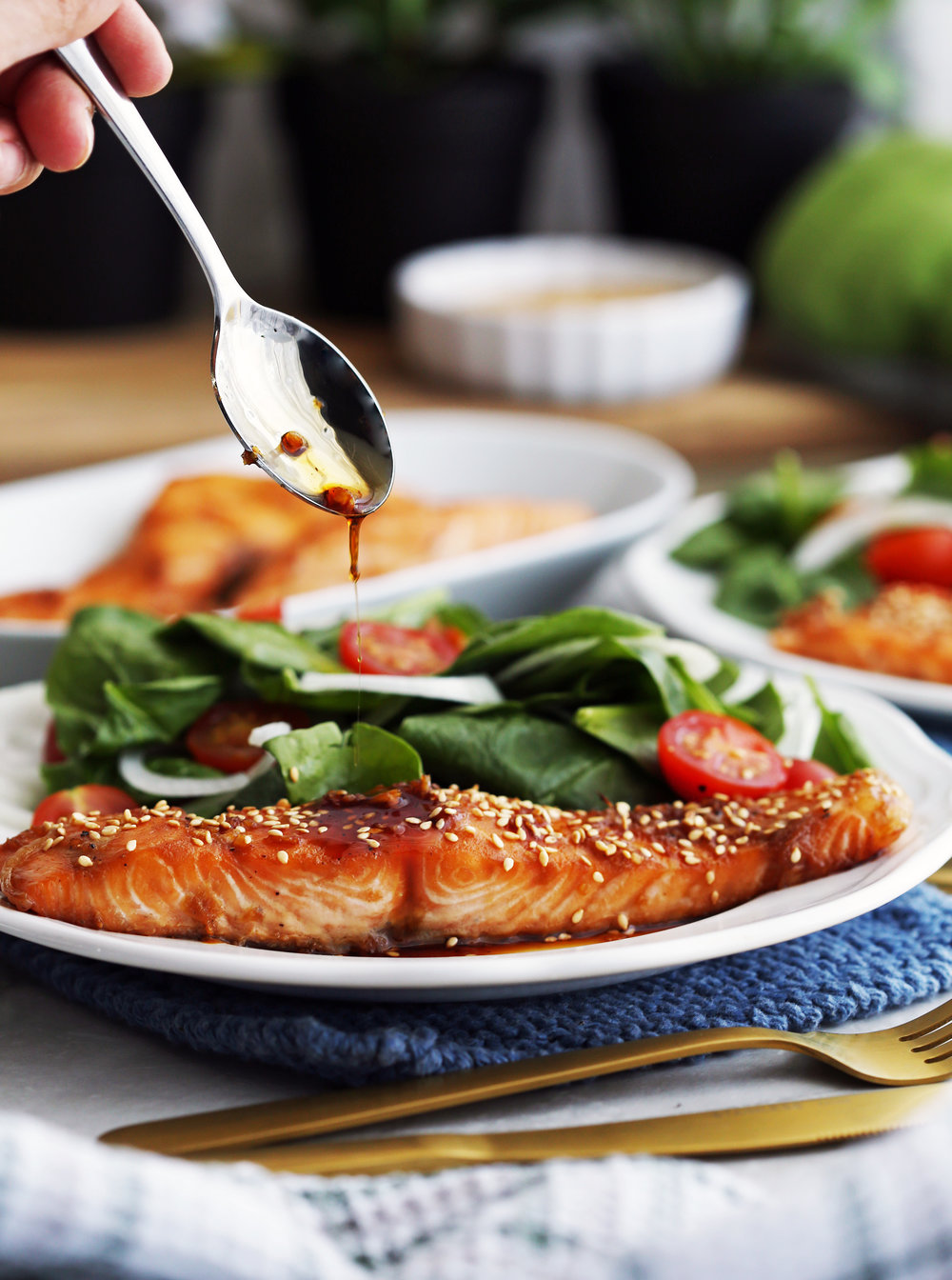 Maple-soy baked salmon on a white plate topped with a spoonful of maple-soy sauce.