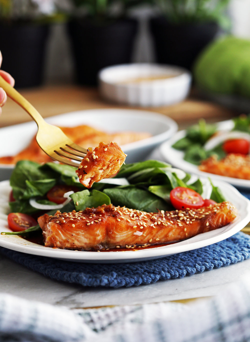 A piece of soy-maple salmon poked with a fork above a top of a plate of a baked salmon with spinach salad.