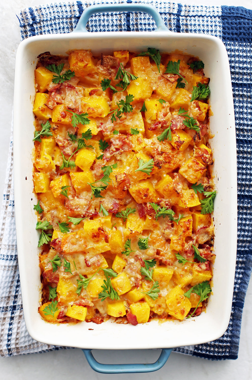 Baked Bacon Cheese Butternut Squash garnished with parsley in a large baking dish.