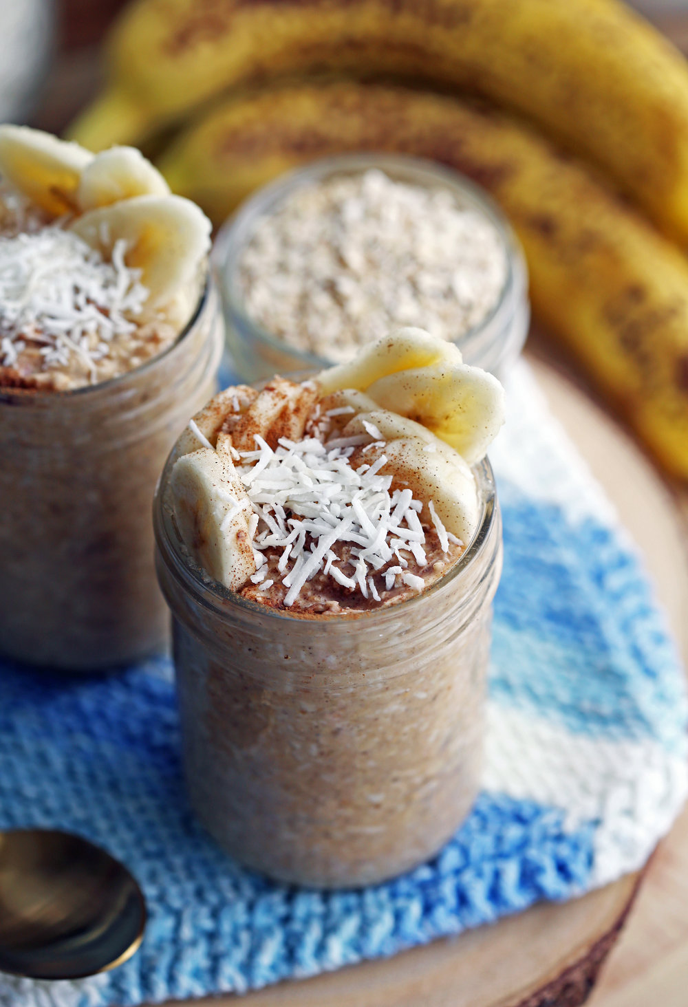 Banana Coconut Cream Pie Overnight Oats topped with bananas, cinnamon, and coconut in a mason jar.
