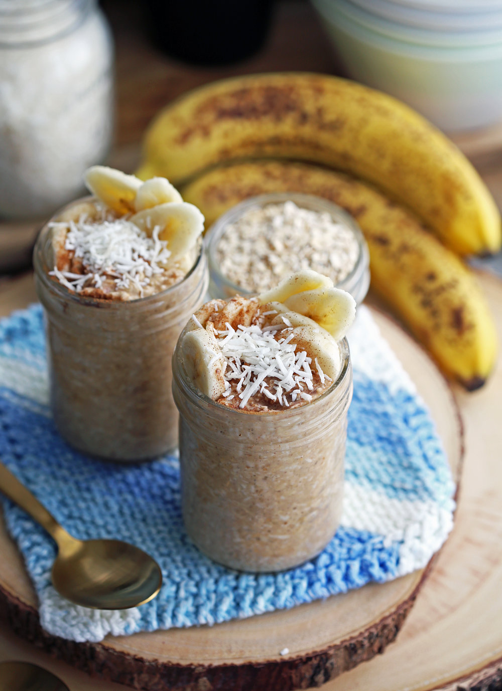 Banana Coconut Cream Pie Overnight Oats topped with bananas, cinnamon, and coconut in two mason jars.