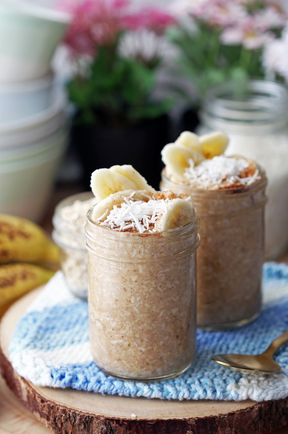 Two mason jars filled with Banana Coconut Cream Pie Overnight Oats.