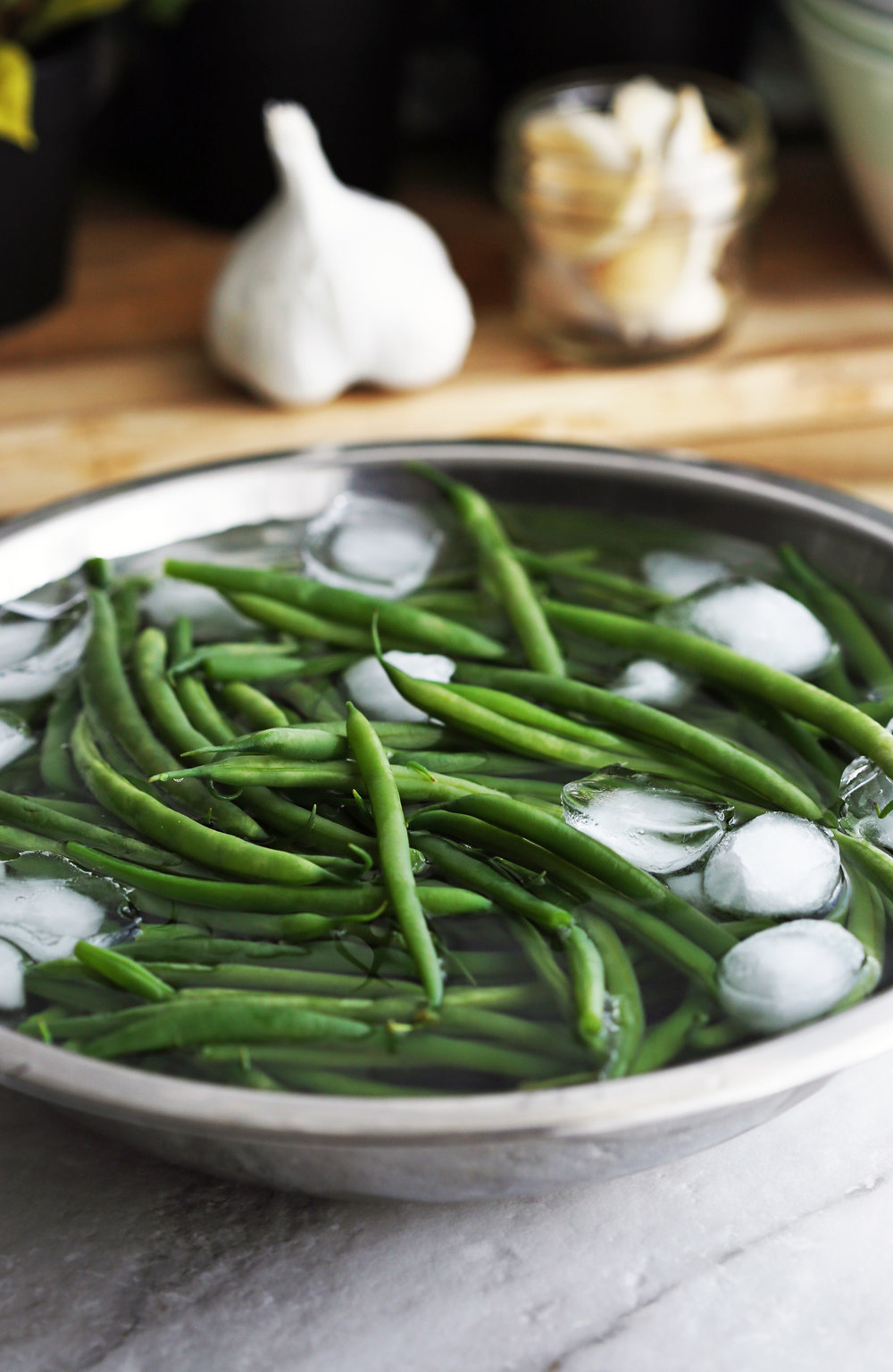 Blanched French green beans in an ice bath.