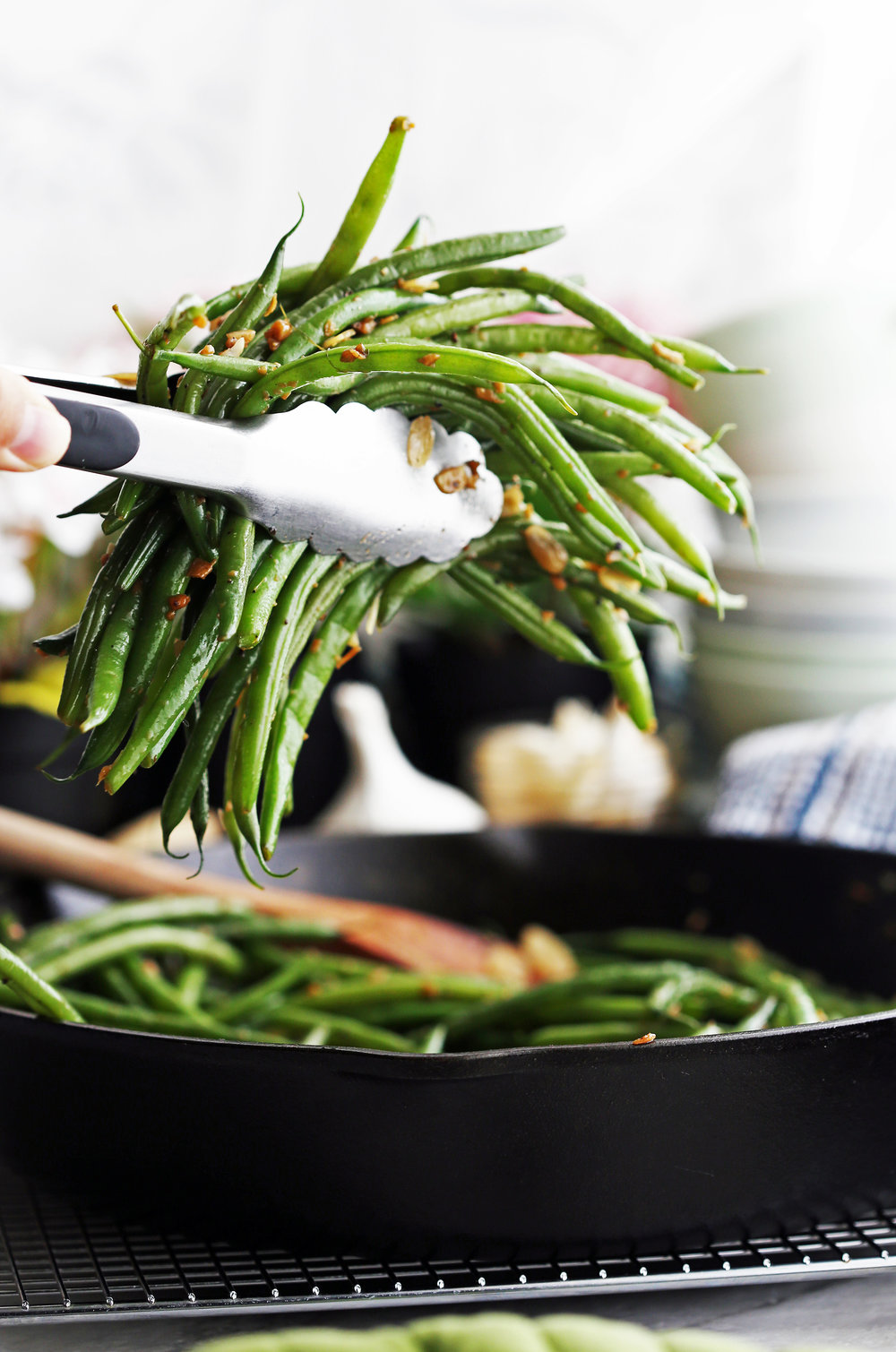 Metal tongs holding garlic ginger green beans with more green beans in a cast iron skillet below.
