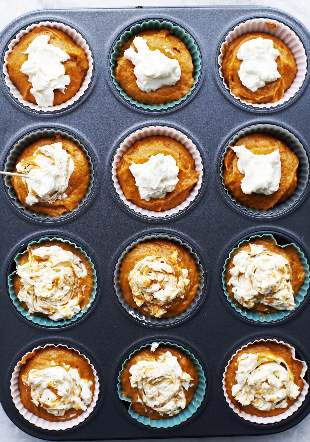 Twelve unbaked pumpkin cream cheese muffins in a muffin pan.
