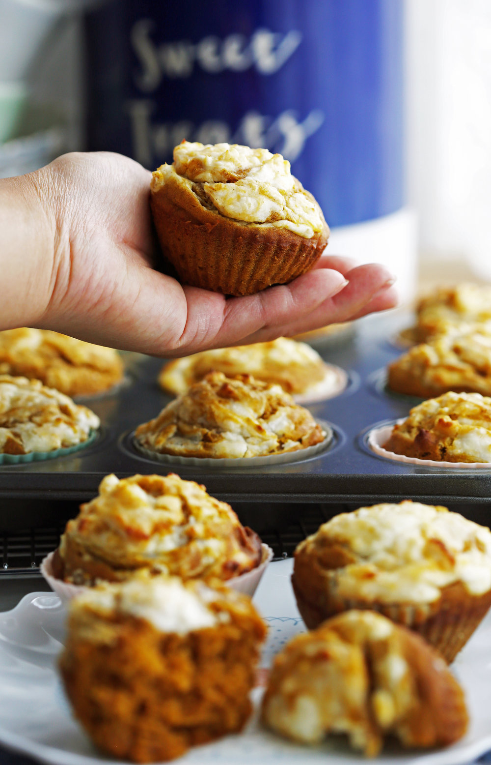 A pumpkin cream cheese muffin held in the palm of a hand with more muffins on a plate and muffin pan too.
