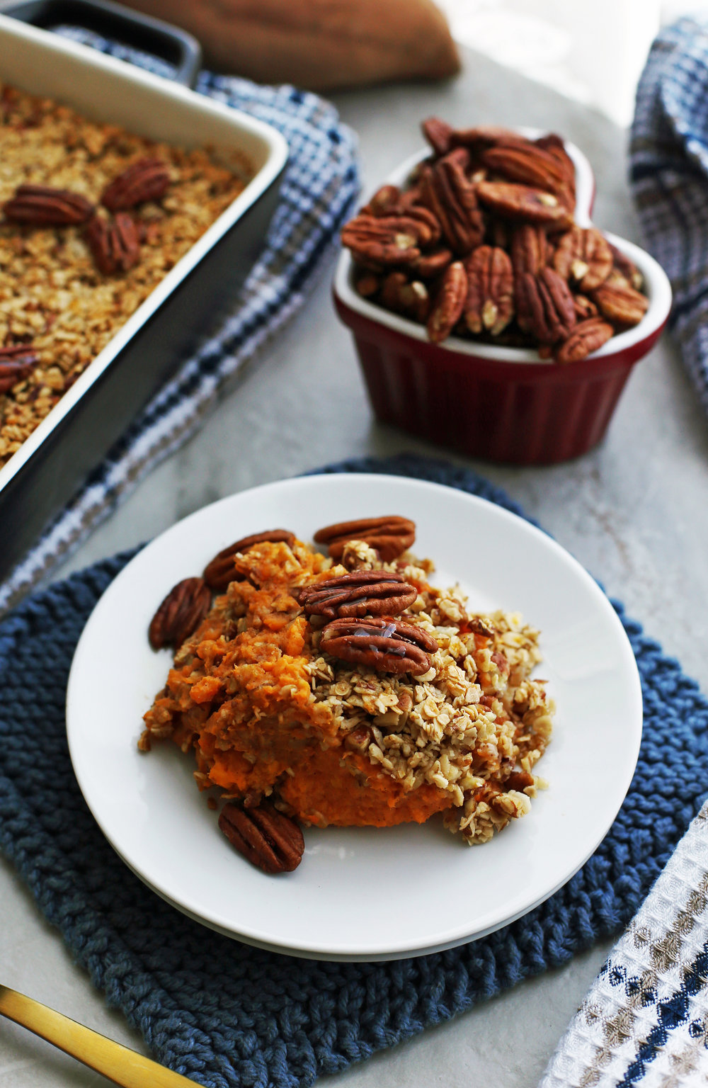 A Sweet Potato Mash with Pecan Oat Topping on a white plate.
