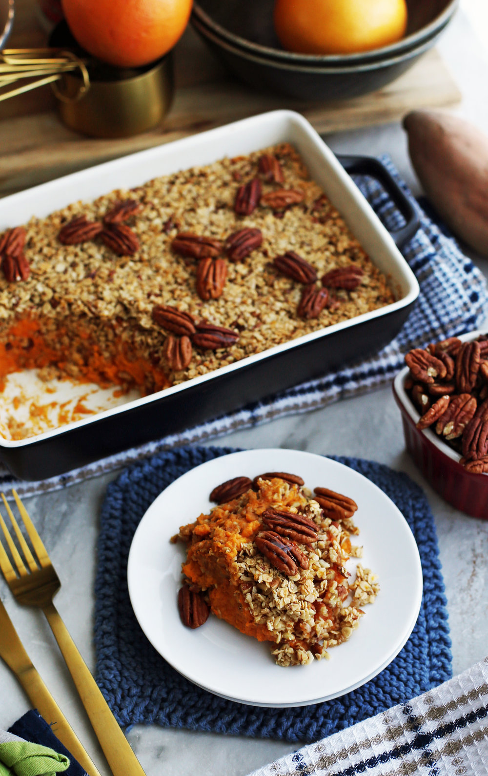 Sweet Potato Mash with Pecan Oat Topping on a white plate and in a black casserole dish.
