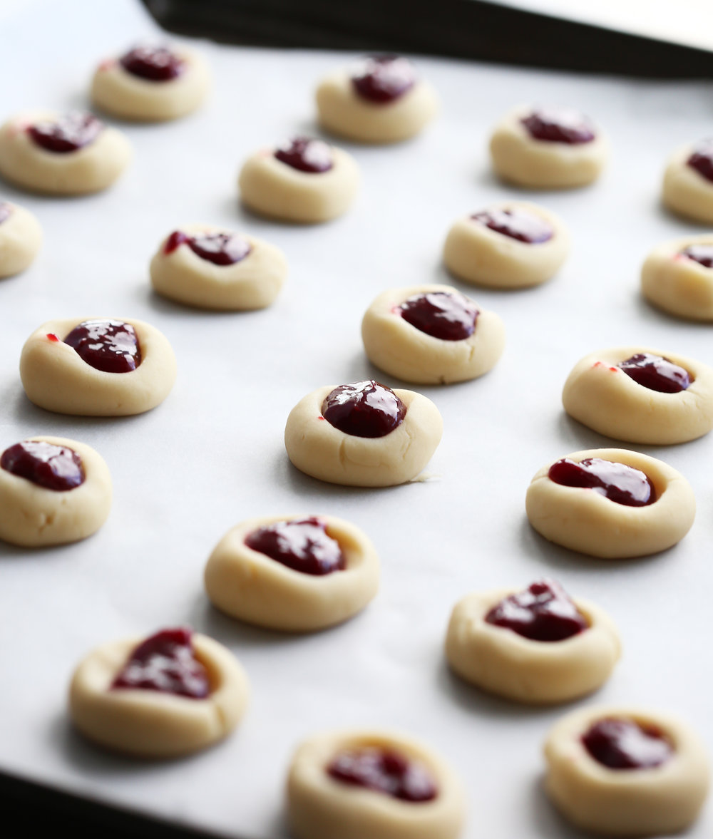 Unbaked shortbread cookies with a thumbprint indentation that's filled with raspberry jam on a baking sheet.