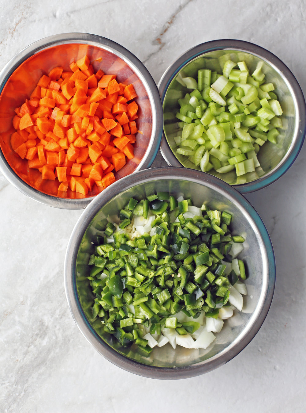 Three metal bowls containing diced peppers, onions, carrots, and celery.