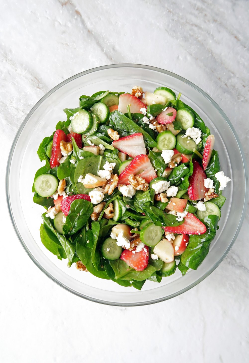 Summer Strawberry Cucumber Spinach Salad that's been tossed with Apple Cider Vinaigrette in a large glass bowl.