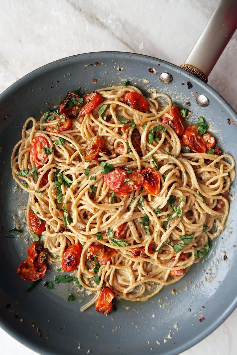 Spaghetti with roasted cherry tomatoes and basil in a skillet.
